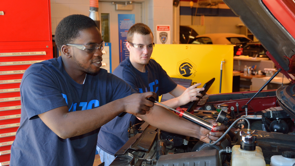 two student working on car